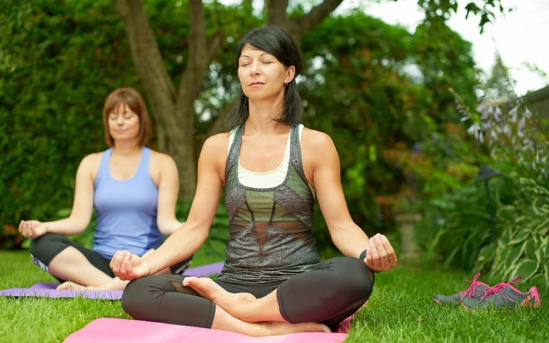52848814 - couple of female friends in their forties connecting and staying healthy by practicing yoga i